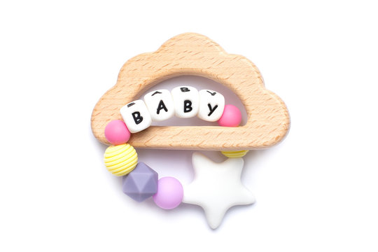 Baby wooden toy and teethers pastel colors on white background