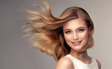Poster Kapsalon Woman with curly beautiful hair on gray background. Girl with beauty a pleasant smile. Short wavy hairstyle