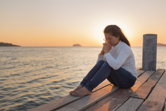 The girl sits in prayer to God with a promise. With love for God At sea ocean Outdoors during the sunset in the winter