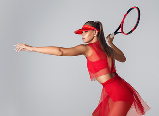 Beautiful and slender girl plays tennis. A fit young woman with a racket in her hand in a red dress for the game.