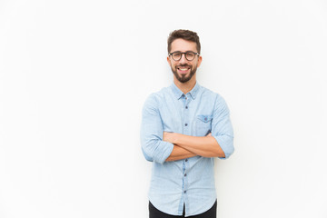 Joyful positive guy posing with arms folded. Handsome young man in casual shirt and glasses standing isolated over white background. Happy man portrait concept Papier Peint