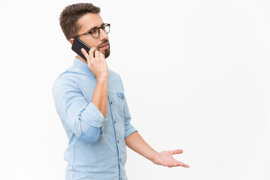 Annoyed guy speaking on mobile phone, arguing with talk partner. Handsome young man in casual shirt and glasses standing isolated over white background. Phone talk concept