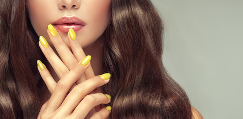 Photo sur Aluminium Manicure Beautiful girl long , curly hair . Model woman showing a yellow manicure on nails . Cosmetics and makeup