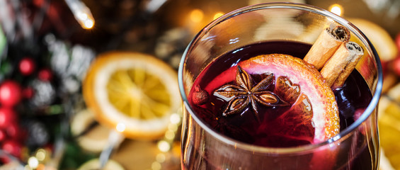 Spoed Foto op Canvas Wijn Christmas mulled close-up in a glass, red wine with spices and fruits oranges on a wooden rustic table with fir branches new year. Traditional hot christmas drink. Selective focus. Copy space