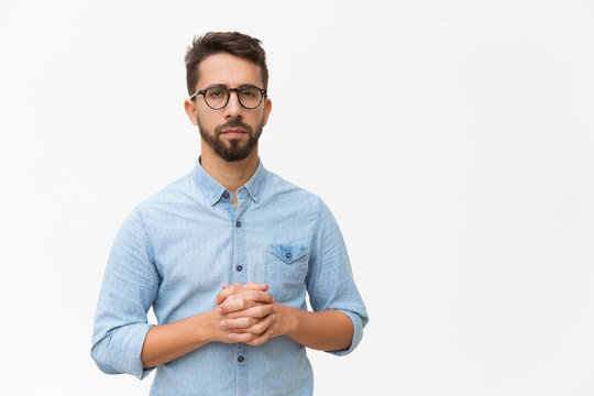 Front of serious confident man with clasped hands looking at camera. Handsome young man in casual shirt and glasses standing isolated over white background. Male portrait concept