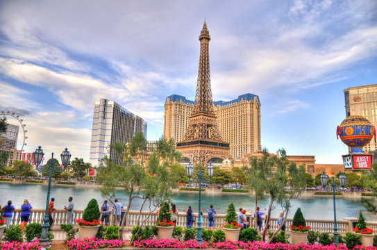 LAS VEGAS, NEVADA, MAY 18: Impressive colorful HDR image of people observing the Bellagio fountain with the background of Paris hotel on cloudy sky. Las Vegas, May 18, 2016