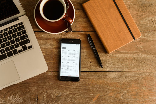 Screen of smartphone with calendar of year 2020 with laptop, pen and note book on coffee table