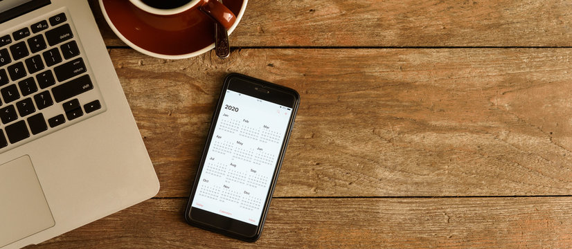 Screen of smartphone with calendar of year 2020 with laptop, pen and organizer on coffee table