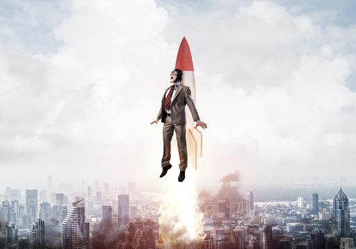 Businessman in aviator hat flying on rocket