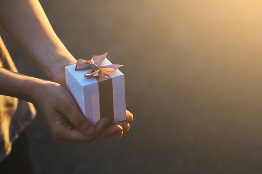 Girl hands holding a small gift wrapped with pink ribbon. Small gift in the hands . concept give happiness .Concept merry christmas and happy new year 2020