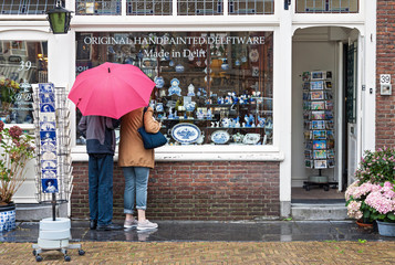 Two tourists with red umbrella looking at window display of traditional Dutch hand painted pottery shop on 25 August, 2018 in Delft, Netherlands