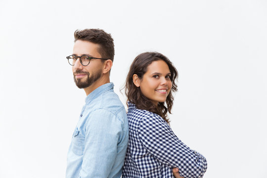 Happy positive couple standing back-to-back, looking at camera, smiling. Young woman in casual and man in glasses in glasses posing isolated over white background. Happy couple concept