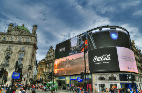 LONDON, UNITED KINGDOM, JUNE 4: colorful dramatic HDR image of the famous Piccadilly Circus with its famous in the center of London on beautiful blue cloudy sky. London, UK, June 4, 2019