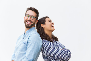 Fototapeta Joyful carefree couple leaning on each other, chatting and laughing at joke. Young woman in casual and man in glasses in glasses posing isolated over white background. Sweet couple concept