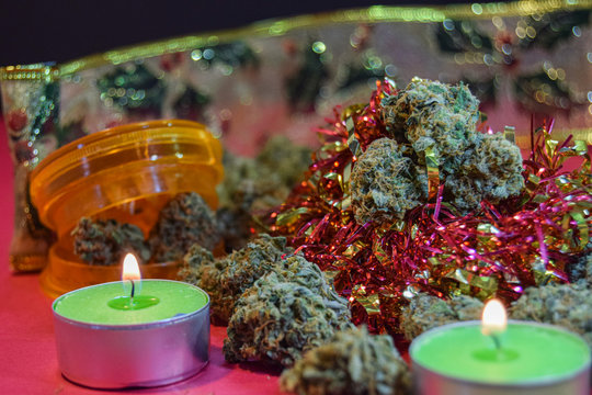 dried cannabis flowers and grinder with christmas decorations to celebrate the new year