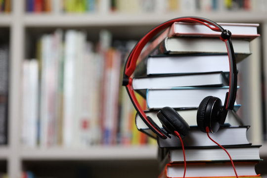 headphones and a stack of books, listening to audio books and traditional reading