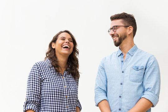 Positive funny guy making his girlfriend laugh. Young woman in casual and man in glasses in glasses posing isolated over white background. Having fun together concept
