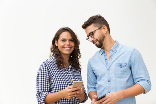 Smiling curious guy in glasses looking at girlfriend cellphone screen. Young woman in casual and man in glasses in glasses posing isolated over white background. Communication concept