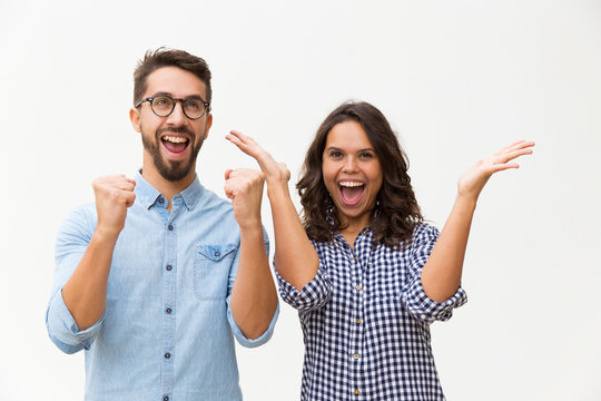 Happy excited couple rejoicing at good news, making winner gestures, celebrating success. Young woman in casual and man in glasses standing isolated over white background. Good news concept