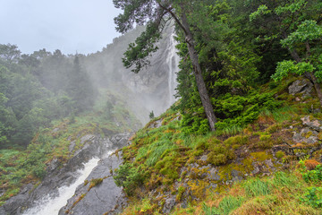 Waterfall in forest green landscape, Norway