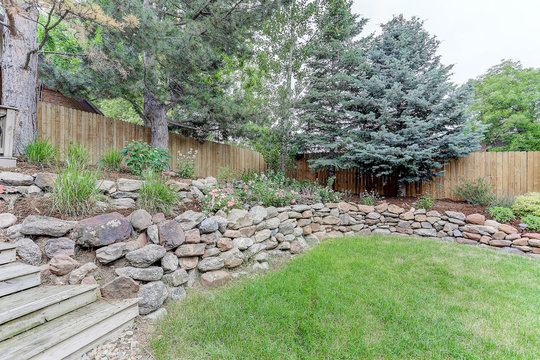 Back yard landscaping with rocks, wooden steps, and fencing