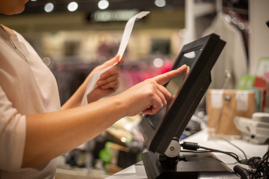 Young woman hands scaning / entering discount / sale on a receipt, touchscreen cash register, market / shop, finance concept, business