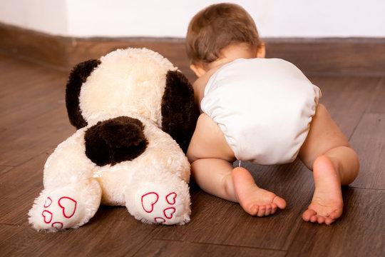 Baby wearing cloth diaper next to puppy dog stuff animal