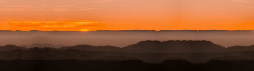 Amazing landscape panorama background from a sunset with fog in the hills - black forest
