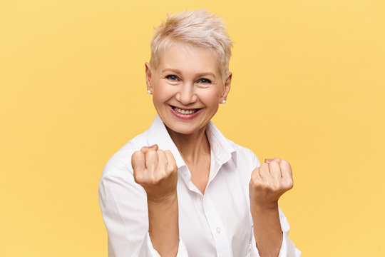 Isolated image of strong independent European businesswoman with short dyed hair expressing positive attitude, smiling confidently, clenching fists. Women, femininity, power, confidence and success