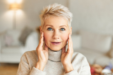 Positive human facial expressions, feelings, emotions and reaction. Picture of emotional attractive mature female with blonde hair and blue eyes holding hands on face, being amazed with something