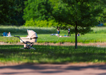 Baby carriage in park with parent nearby