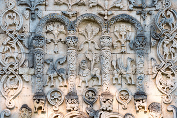 Arched wall in church with carved characters.