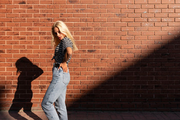 Side view portrait of young blonde girl in gey t-shirt and jeans that syands in the sun, holds her hands on her waist, isolated over red brick wall
