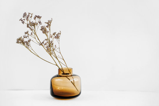 Branch flowers in a glass vase on white table. Decor for interior. Stylish decoration for home.