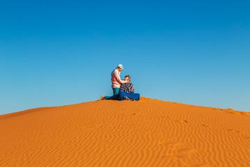 Loving couple in the Sahara desert. Joint rest.