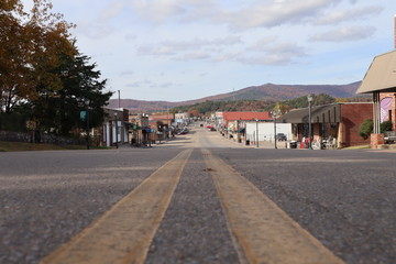 A street-level perspective view down a small town main street, Mena Street, Mena, Arkansas, with autumn colors on Rich Mountain in the background, small town America
