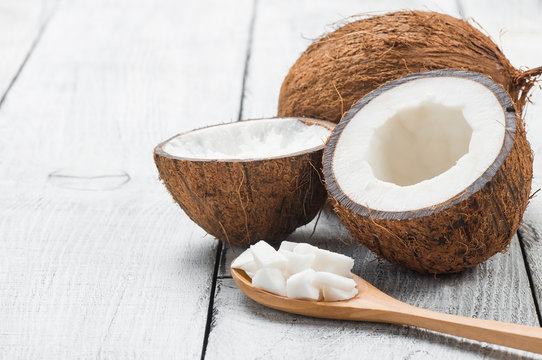 Organic natural whole and cracked coconut fruit and pieces of coconuts in wooden spoon on white wooden background, tropical healthy food concept, Cocos nucifera