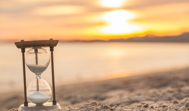 Hourglass in the sunset golden hour. Sand passing through the glass bulbs of an hourglass measuring the passing time as it counts down to a deadline or closure on a sunset/ sunrise beach background.