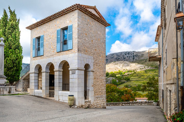 A narrow historic building with French Bleu shutters in the medieval hilltop village of Gourdon, France, in the mountains of Provence