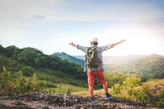 An old man carrying a backpack, hiking and standing on a high mountain He is happy. Senior travel concept
