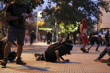 Protesters take cover during clashes with security forcers at a protest against Chile's government in Santiago