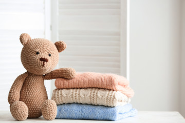 Stack of clean kid clothes with toy on table in room