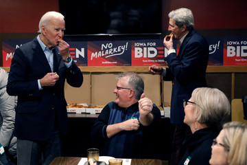 "Democratic 2020 U.S. presidential candidate and former U.S. Vice President Joe Biden and former 2004 Democratic presidential nominee John Kerry eat pizza boxes after an event on Biden's ""No Malarkey!"" campaign bus tour in Decorah, Iowa"