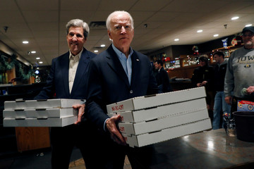 "Democratic 2020 U.S. presidential candidate and former U.S. Vice President Joe Biden and former 2004 Democratic presidential nominee John Kerry carry pizza boxes after an event on Biden's ""No Malarkey!"" campaign bus tour in Decorah, Iowa"
