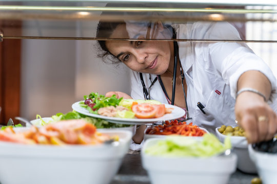 Medical doctor bent over with a salad plate picking up food at a self-service restaurant