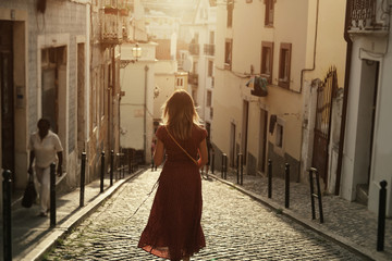 Young traveling woman wearing long red dress walking on Lisbon streets looking at beautiful view Wall mural