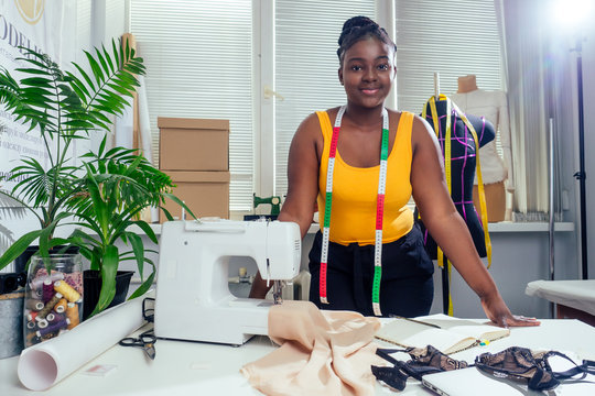Young african american dressmaker woman sews clothes on sewing machine at tailor office it tropical summer style
