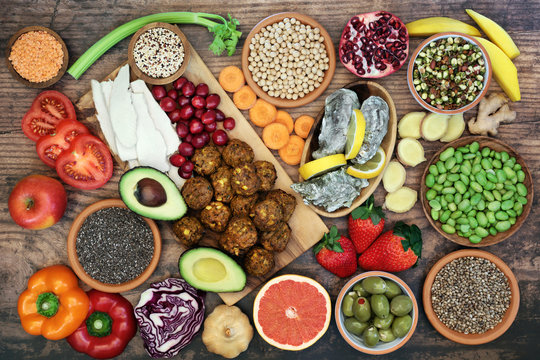 Super food for a healthy eating concept with health foods high in antioxidants, anthocyanins, vitamins, minerals, protein, smart carbs, omega 3 and fibre. Flat lay on rustic wood background.