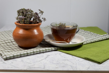 A cup of tea with a floating oregano flower stands on a white saucer, on which lies a silver spoon. Next to the cup is a clay pot with a bouquet of oregano.