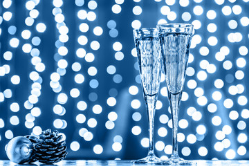 Wall Mural - Two glasses of champagne with Christmas toys. Festive lights bokeh Christmas background in classic blue. New Year holidays celebration. Horizontal, toned